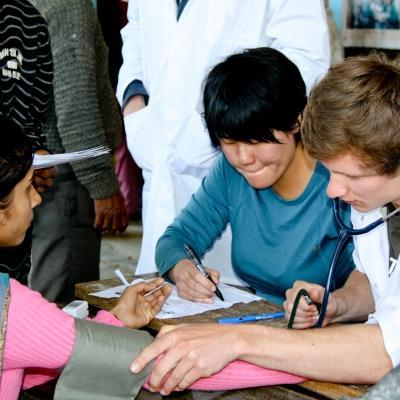 An intern participates in health screenings as part of their medical work experience in Nepal.